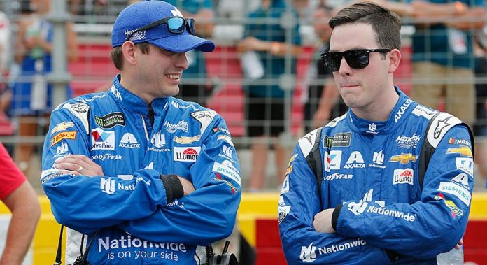 Crew chief Greg Ives, left, and driver Alex Bowman chat on the pre-race grid at Charlotte Motor Speedway.