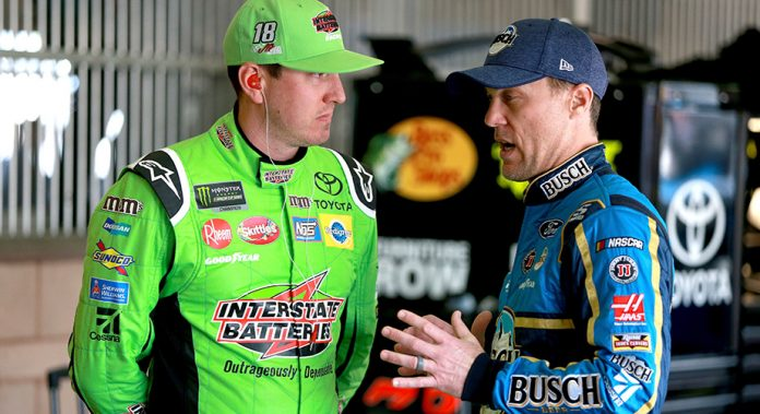 Kyle Busch and Kevin Harvick talk in the garage at Auto Club Speedway.