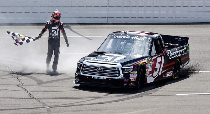Kyle Busch fetches the checkered flag after winning the Truck Series race at Pocono.